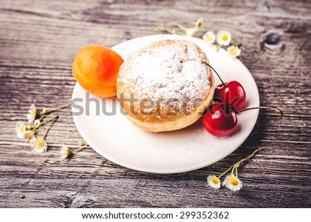 Donut on white plate  with fruits on wooden background - stock photo