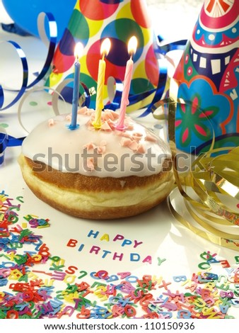 Donut with glaze, topping and birthday candles - stock photo