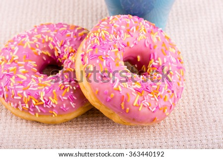 Donut with pink glaze and many decorative sprinkles along with  brlue coffee cup on a piece of fabric. - stock photo