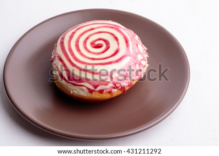 donut with spiral frosting on brown plate - stock photo
