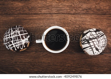 Donuts and coffee cup top view on wooden table - stock photo