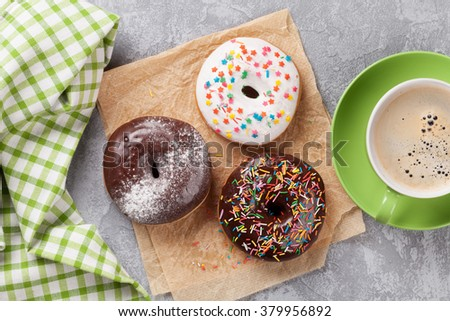 Donuts and coffee on stone table. Top view - stock photo