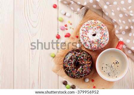 Donuts and coffee on wooden table. Top view with copy space - stock photo