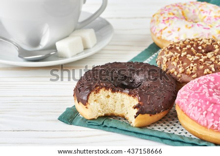 Donuts and cup of coffee on wooden background