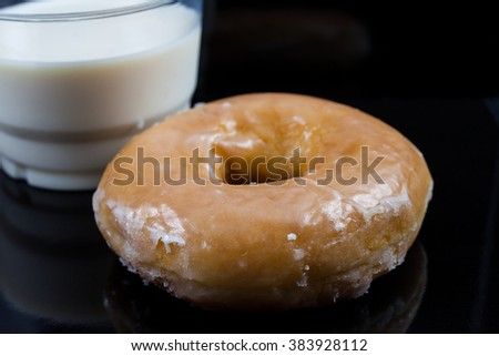 Donuts and milk for breakfast on black background.
