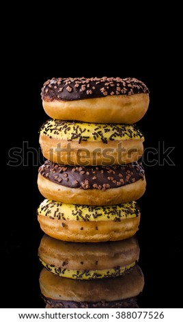 Donuts on reflection table, dark picture, chocolate and banana donuts - stock photo