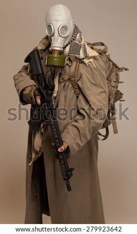 DOOMSDAY SURVIVOR | Environmental disaster. Post apocalyptic survivor in gas mask with rifle and backpack. - stock photo