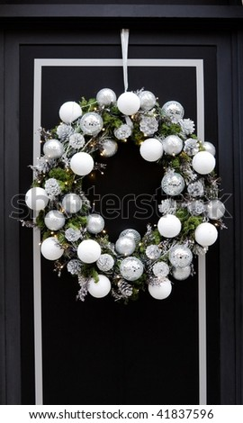Door framed with white shiny Christmas wreath,  lights and pin econes. - stock photo