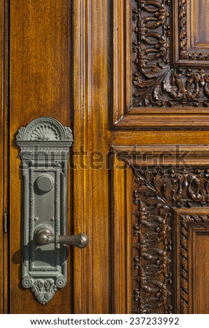 Door handle on solid wood door - stock photo