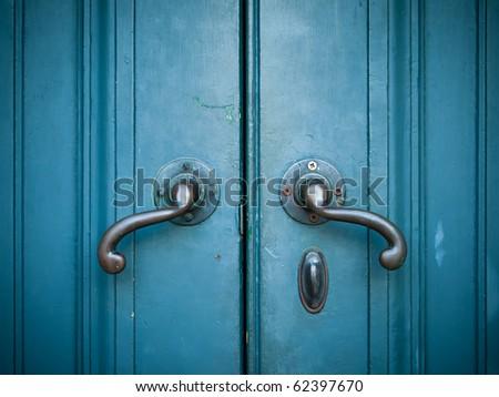 Door handles with an old double door painted with blue - stock photo
