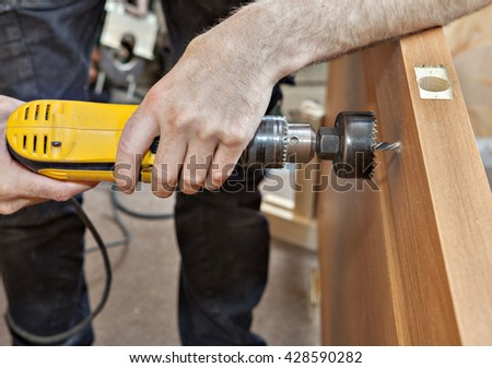 Door installation, hands carpenter holding yellow  power drill with wood hole saw drill bit, drilling through the door to set the lock with a handle, close-up.  - stock photo