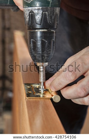 Door installation, Woodworker install door butt hinges  using a screw gun drill driver, close-up. - stock photo