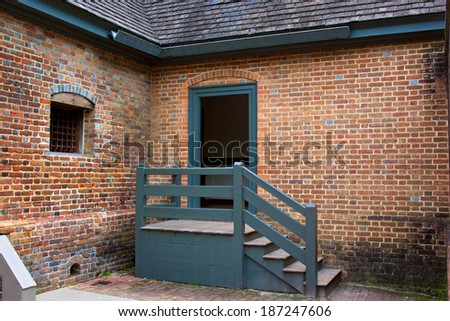 Door leads into the depths of the jail in Virginia's Colonial Williamsburg. - stock photo