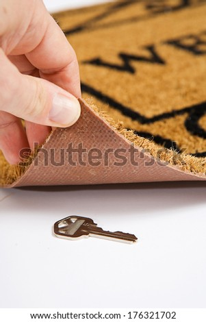 Door Mat: Finding House Key Under Door Mat - stock photo