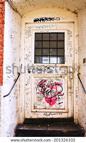 Door of  antique building covered by graffiti - stock photo