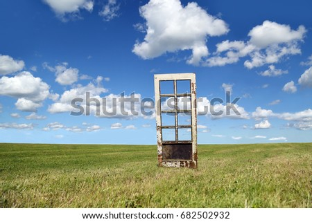 Door, old and scratched, stands alone in green field under blue cloudy sky