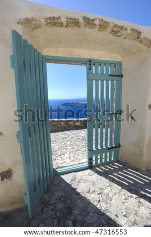 door open with a sea view, from a courtyard in Santorini, Greece - stock photo