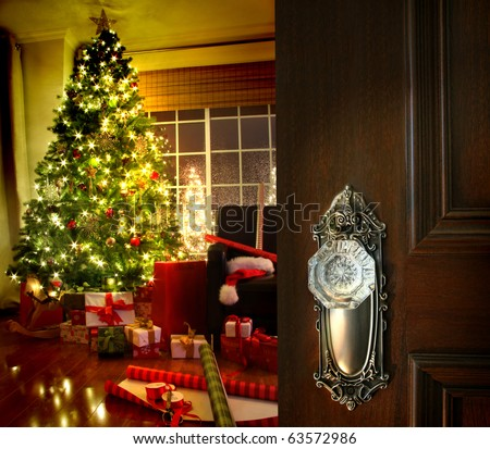 Door opening into a beautiful living room decorated for Christmas - stock photo