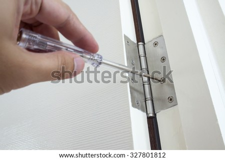Door repairing. Close-up of repairing door hinge. - stock photo