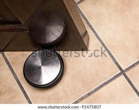 Door stopper closeup on ceramic floor - stock photo