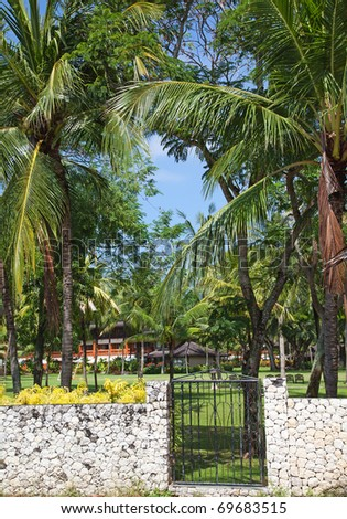Door to paradise (tropical garden with a luxury villa at background) - stock photo