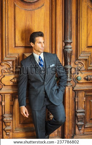 Door to Success. Dressing in a dark blue three piece suit, patterned necktie,  a handsome, sexy, middle age businessman is standing by an old fashion style office door way, thinking, lost in thought.