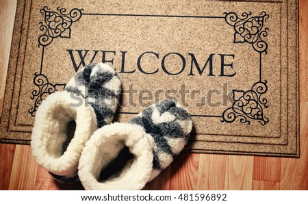 "Doormat in vintage style with inscription ""Welcome"". Cleaning foot carpet with shoes made of sheep wool"
