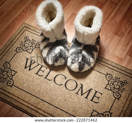 Doormat with text Welcome. Cleaning foot carpet with shoes made of sheep wool - stock photo
