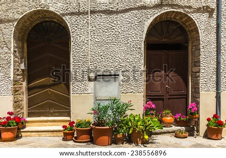 doors decorated with flowers in tuscan village - stock photo