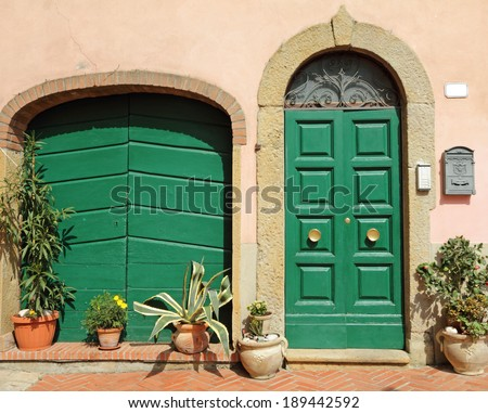 doors decorated with flowers in tuscan village Montescudaio - stock photo