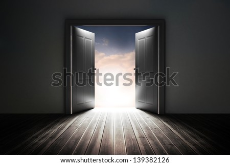 Doors opening to reveal beautiful sky in dark grey room - stock photo