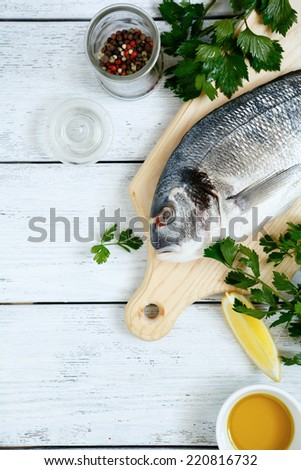 Dorado fish with lemon, olive oil and herbs, top view - stock photo
