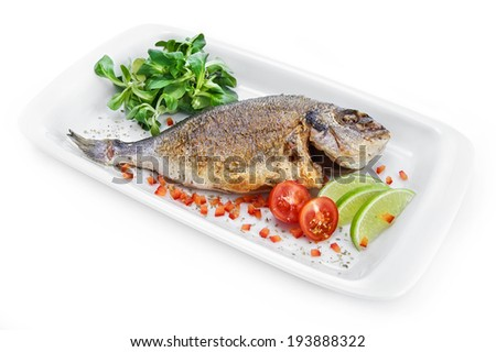 Dorado served with light-green mix, cherry tomatoes & Tar-tar sauce in the shell of sea salt on the plate isolated on white background - stock photo
