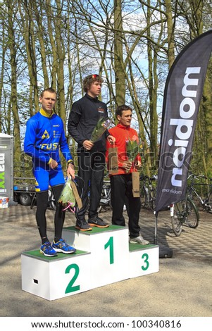 DORDRECHT, NETHERLANDS - APRIL 14 2012: Run Bike Run Bike Run duathlon event. Mark Hamersma, Jorik van Egdom and Ivo Bijl on the winners podium of the dualthlon on Saturday 14 April 2012 in Dordrecht. - stock photo