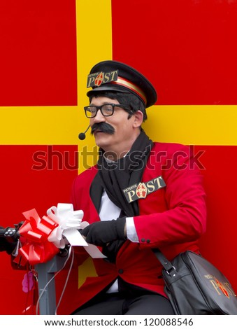 DORDRECHT, THE NETHERLANDS - NOVEMBER 18: Man dressed as the postman of Santa Claus driving his post van in a parade on the streets of Dordrecht on November 18, 2012 in Dordrecht, Netherlands. - stock photo