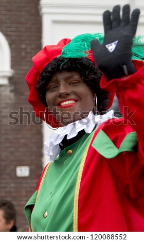 DORDRECHT, THE NETHERLANDS - NOVEMBER 18: Woman dressed as Black Piet waving to the children in a parade on the streets of Dordrecht on November 18, 2012 in Dordrecht, Netherlands. - stock photo