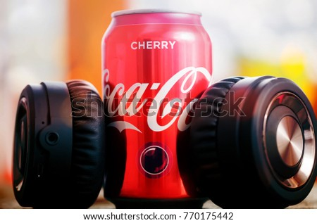 DORKOVO, BULGARIA - DECEMBER 03, 2017: Coca Cola can and music headphones. Coca Cola drinks are produced and manufactured by The Coca-Cola Company, an American multinational beverage corporation.