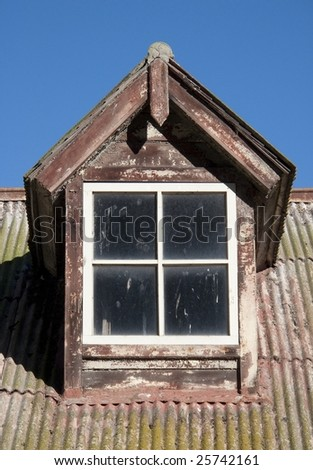 Dormer window on corrugated metal roof against blue sky - stock photo