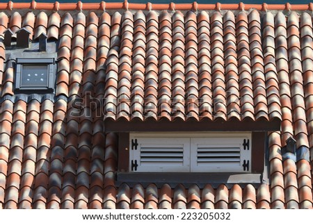 dormer window shuttered in a tile roof, horizontal close-up   - stock photo