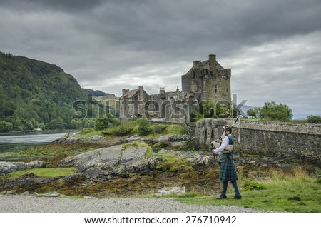 DORNIE, SCOTLAND - SEP 6 2014: A bagpipe player with traditional kilt in front of Eilean Donan, the most famous castle in Scotland, on September 6, 2014 in Dornie, Scotland, United Kingdom.