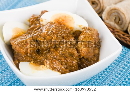 Doro Wat - Ethiopian red chicken stew cooked with onions and berbere (chili and spices mix), topped with hard-boiled eggs. Served with injera. - stock photo