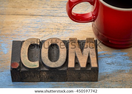 dot com business internet domain - text in vintage letterpress wood type blocks with a cup of coffee - stock photo