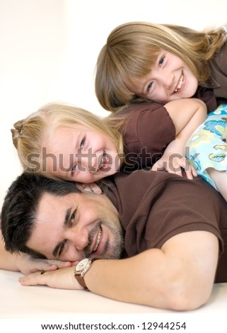 Doting father and his two adorable daughters posing together in a studio. Vertically framed shot - stock photo