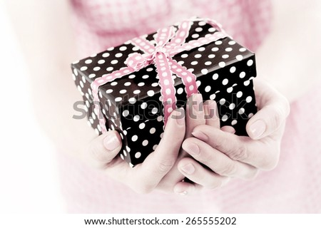 dotted present box in woman hands - stock photo