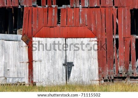 Double barn doors are boarded shut and historic building is abandoned.  Red, wooden, weathered and overgrown, this barn is derelict and dejected.