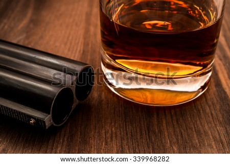 Double-barreled shotgun barrel and glass of whiskey close-up. Focus on the barrel