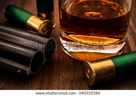 Double-barreled shotgun barrel and glass of whiskey with ammo close-up. Focus on the barrel