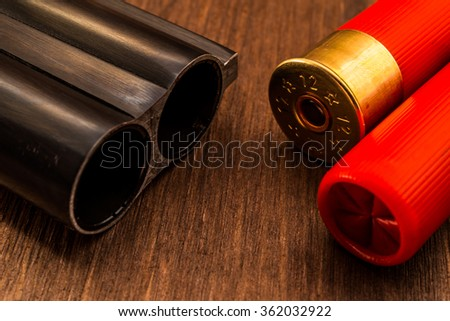 Double-barreled shotgun barrel and two red cartridges. Close up view - stock photo