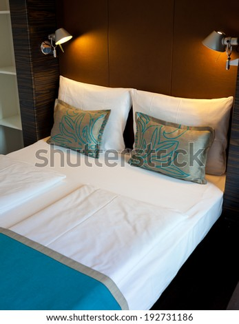 Double bed in the hotel room with soft light - stock photo