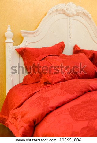 Double bed with pillows in red color. - stock photo